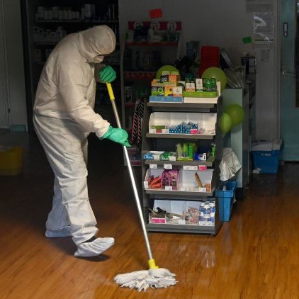 A person in PPE mops a floor