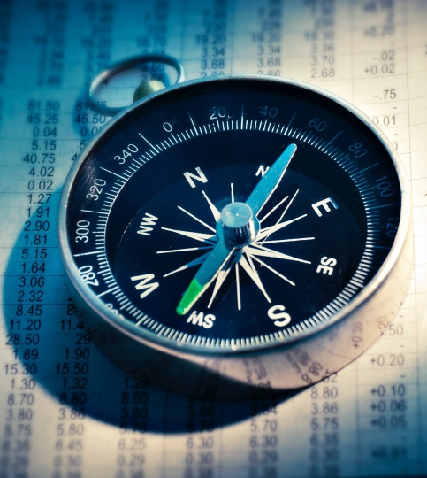 magnetic compass lying on a paper spreadsheet