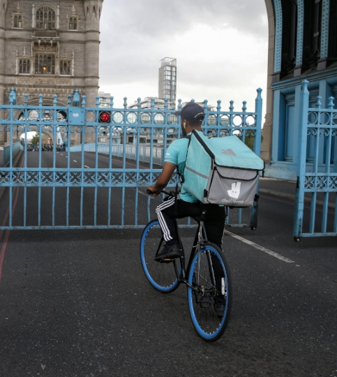 A deliveroo rider waits at Tower Bridge in London