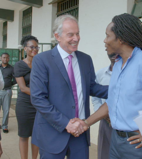 Tony Blair and David Sengeh greet each other at Prince of Wales school in Freetown, Sierra Leone