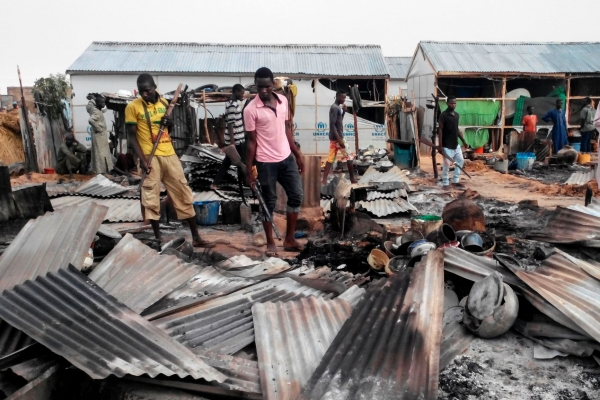 Armed members of a local defence group inspect the damages of a suicide blast in Maiduguri, Nigeria, on June 8, 2017.