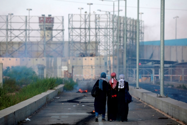 Palestinian protestors walk towards the border during a demonstration at the Erez crossing with Israel on September 18, 2018.