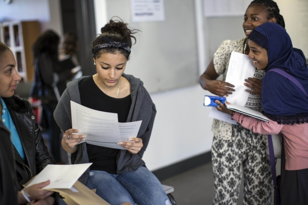 Girls react while opening their GCSE results on August 21, 2014 in London, England.