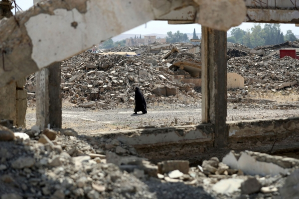 A displaced Iraqi woman walks past destroyed buildings south of Mosul on May 26, 2017, as government forces continue their offensive to retake the city of Mosul from ISIS.