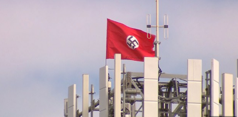 Swastika flag with the words Covid-19 flowing from telecommunications mast in Melbourne