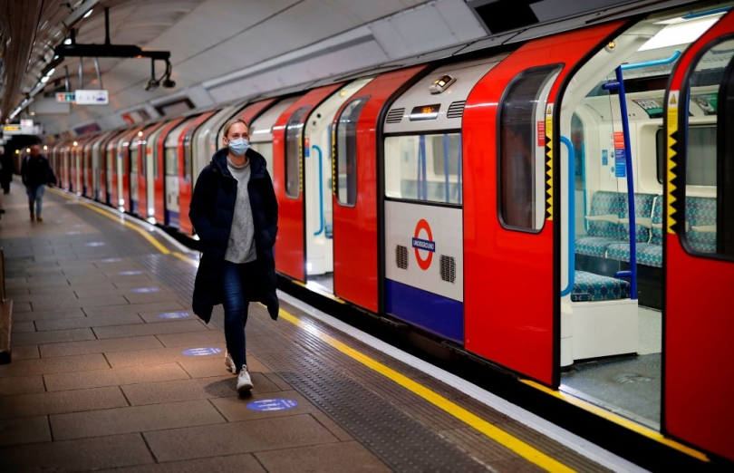 A man in a mask walks along a Victoria line platform. A train with open doors is on the platform next to him.