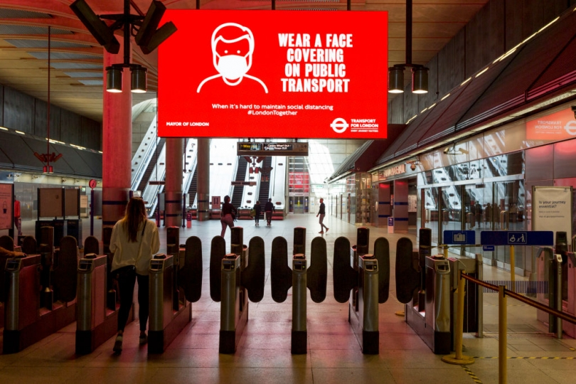 "A digital billboard above a set of fare gates at a TfL station reads ""Wear a face covering on public transport"""