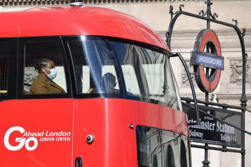 A woman in a face mask rides on the upper deck of a London bus.