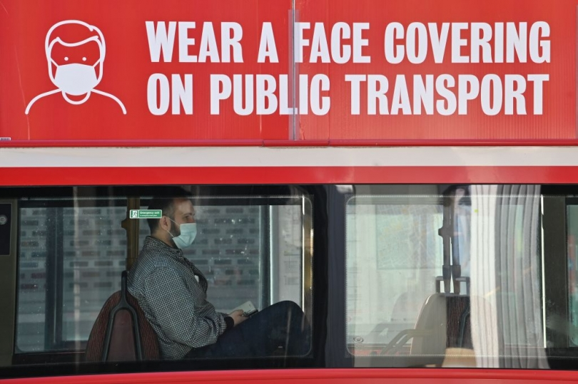 "A man in a mask rides on the lower deck of a London bus with the same TfL PSA from before advertised on the side: ""Wear a face covering on public transport."""