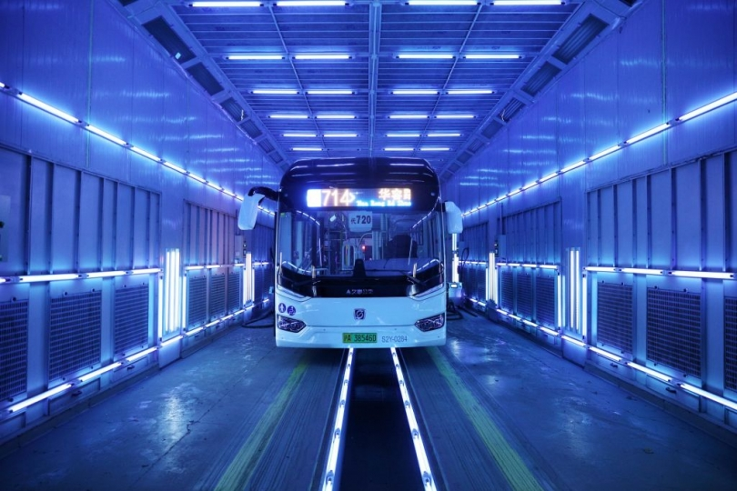 A large coach in China drives through a narrow tunnel illuminated by fluorescent tube lights.