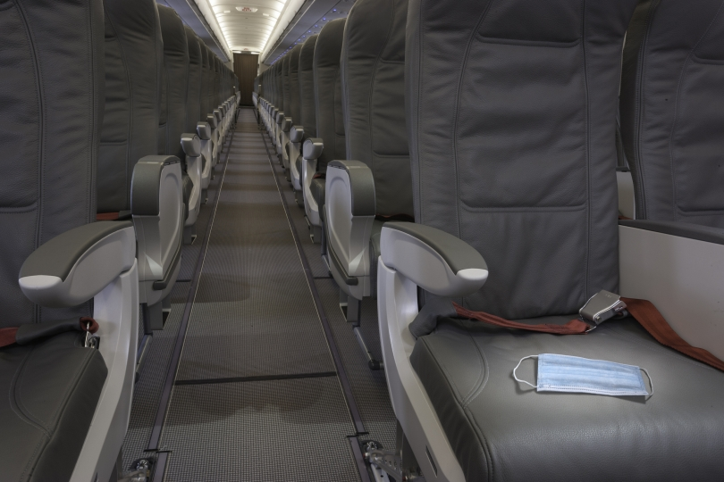 The aisle of an empty passenger airplane. A disposable face mask sits on the first seat illuminated by an overhead light.