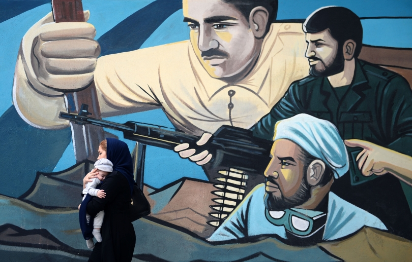 Iranian mother with baby walks past a wall mural celebrating militancy.