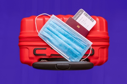 image of a red suitcase with a covid mask and passport resting on top