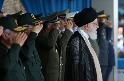Iran's Ayotollah Khamenei standing with IRGC members standing behind him and saluting