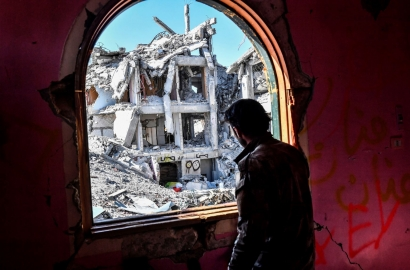 A member of the Syrian Democratic Forces (SDF), backed by US special forces, looks out from a building at the frontline in Raqqa on October 16, 2017 in ISIS' crumbling stronghold.