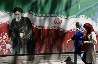 Two people walk past an outside mural showing Ayatollah Ruhollah Khomeini against an Iranian flag