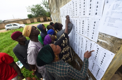 Voters search for details on placards attached to a wall