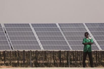 A man stands in front of solar panels in Burkina Faso
