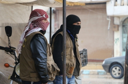 Two men stand under a canopy in the streets of Afrin in Syria, looking solemn