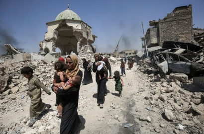 Iraqis walk by the destroyed Al-Nuri Mosque as they flee from the Old City of Mosul on July 5, 2017, during the Iraqi government forces' offensive to retake the city from ISIS fighters.