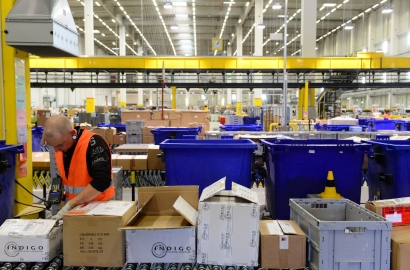 A worker registers products at a distribution warehouse for a large online retailer