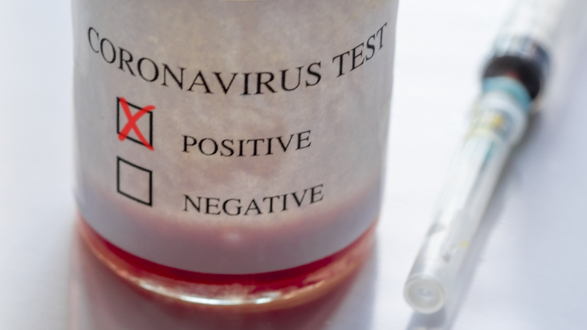 A syringe and bottle with Coronavirus test and a cross in a 'positive' box