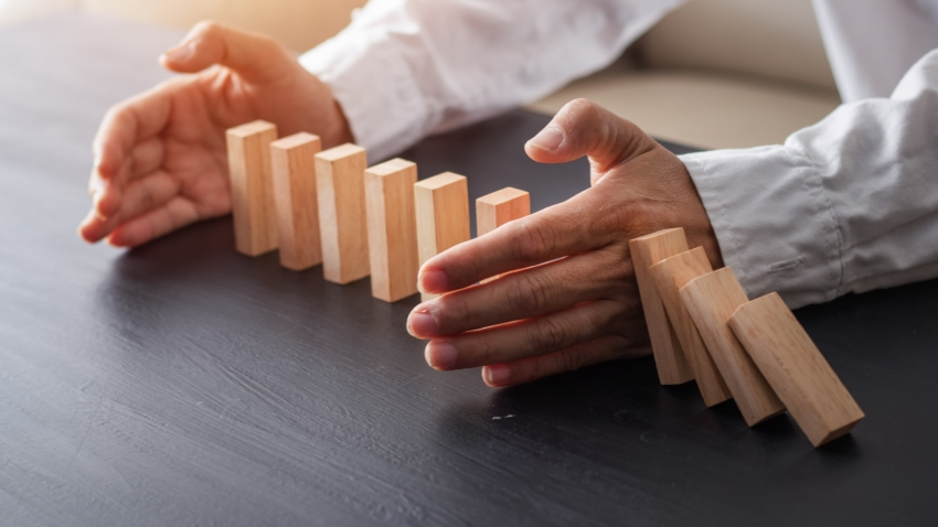 A pair of hands hold up a row of falling dominoes