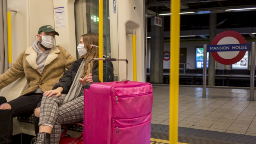 Two people sit on a London Underground train wearing masks