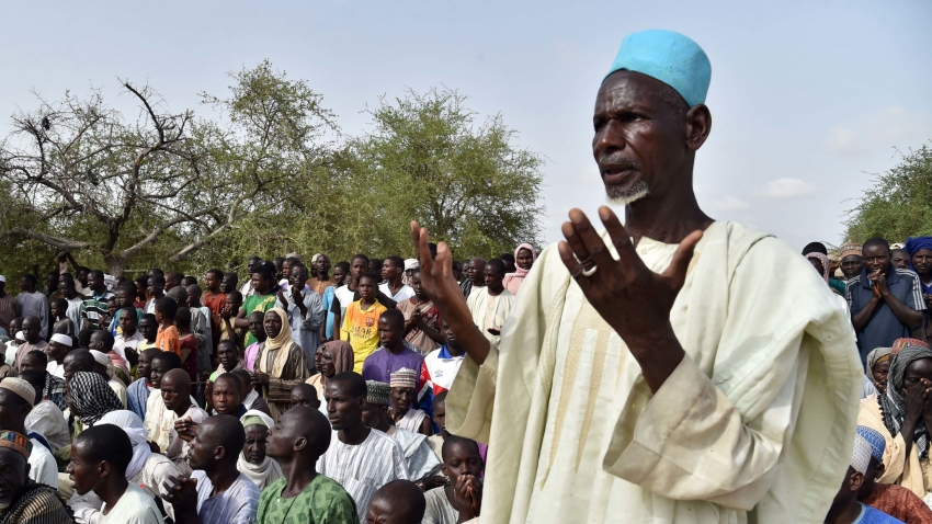 A man stands as residents listen to Niger's Interior Minister Mohamed Bazoum in the village of Toummour near Bosso