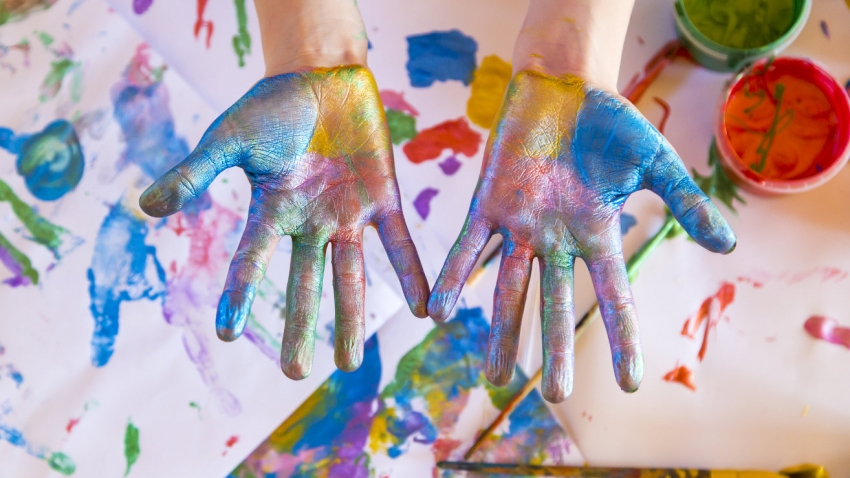A pair of hands covered in bright coloured paints