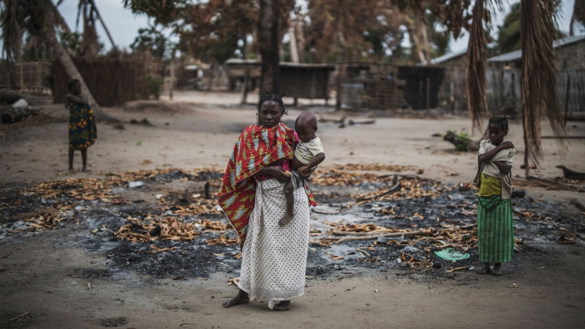 a woman in a village holds her infant in front of a charred patch of ground while two people look on