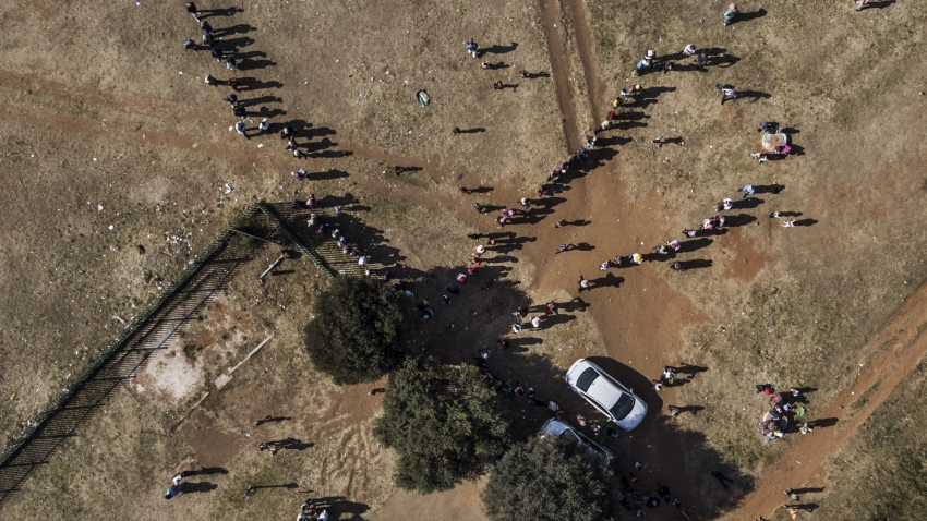 "This aerial view shows residents of the Zamimpilo informal settlement queuing during a food distribution by the non profit organisation and charity group ""Hunger has no Religion"", in Johannesburg"