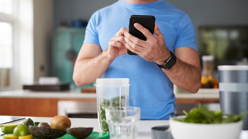 man using mobile device in the kitchen