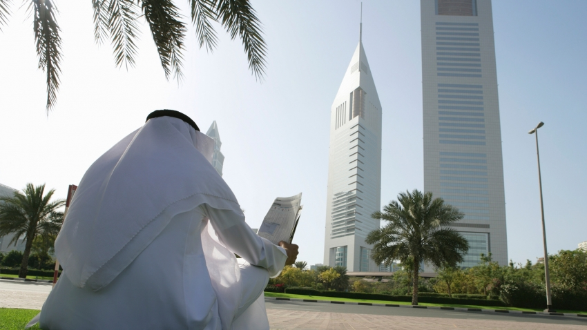 Arab man reading a newspaper in a park in Dubai