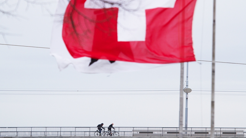 two cyclists biking underneath the flag of Switzerland