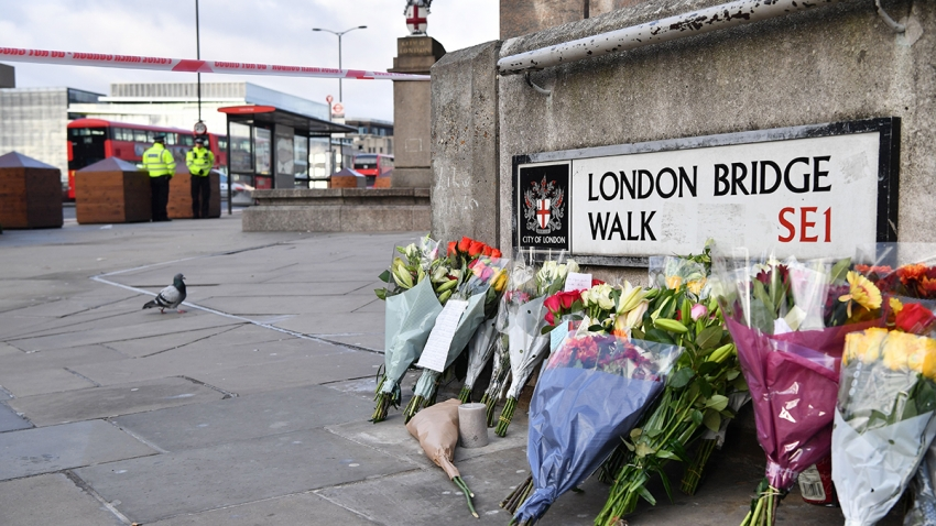 police officers stand inside a cordon beside floral tributes left close to London Bridge following November 2019 terrorist attack