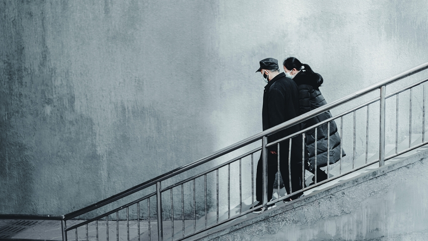 A man and woman wearing face masks walk down stairs