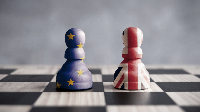 two chess pieces, one painted with EU flag and one painted with British flag