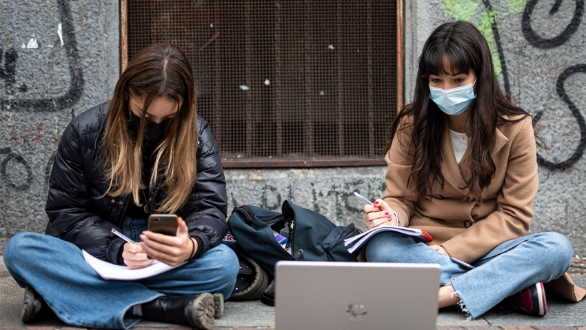 Two students of high school Gioberti sit on the sidewalk with a laptop to follow a distance learning (DaD) lesson on the street outside their school to protest against schools closures imposed by the government due to an increase in COVID-19 coronavirus disease infections.
