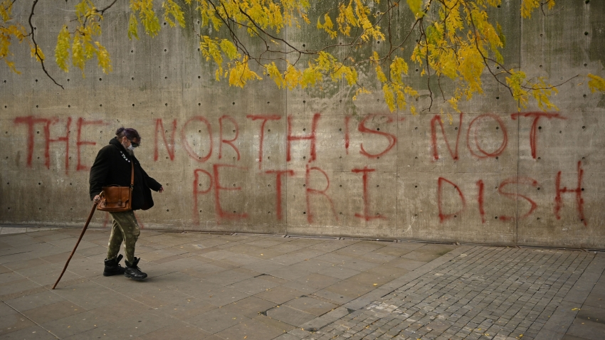 A woman wearing a face-mask walks past graffiti declaring that 'the north is not a petri dish' after Greater Manchester mayor Andy Burnham threatened legal action if Tier 3 restrictions are imposed on the city without agreement, in Piccadilly Gardens, central Manchester on October 16, 2020