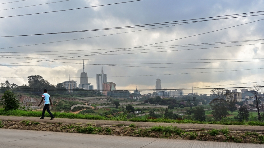 view of nairobi skyline through powerlines with man walking down the street