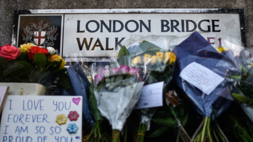 flowers in front of a sign for London Bridge Walk