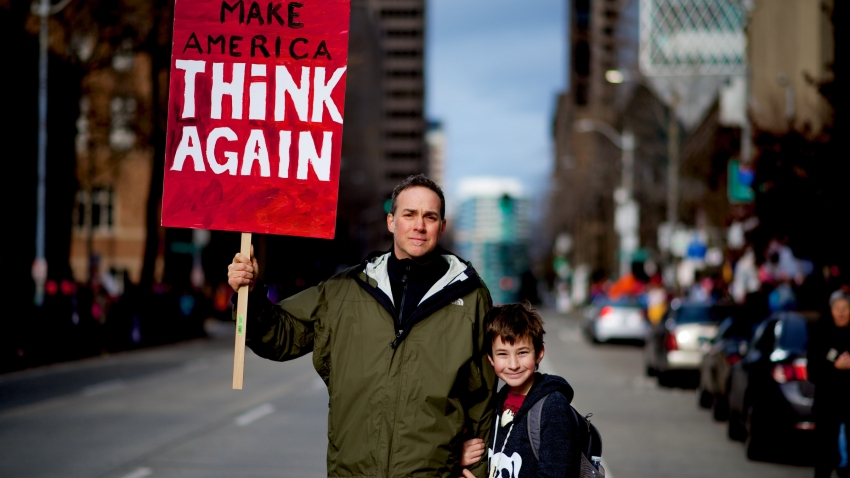 photo of a man and boy holding a sign that says Make America Think Again