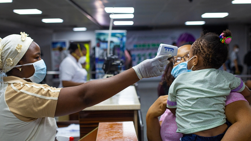 A mother and child body temperatures are being tested at the gate of entry upon arrival at the Murtala International Airport in Lagos