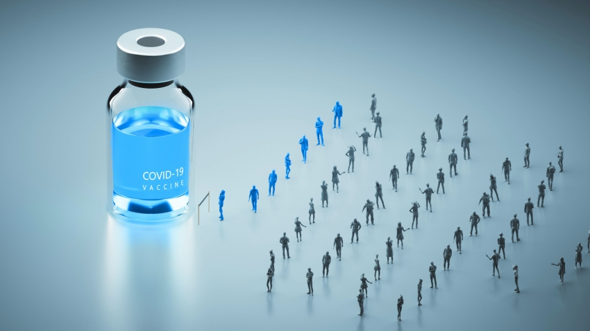 blue figures look up at a vial of Covid-19 vaccine