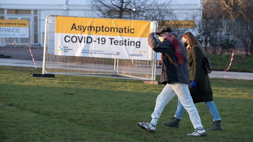 a man and a woman walk together along a grassy park towards an Asymptomatic Covid-19 testing centre
