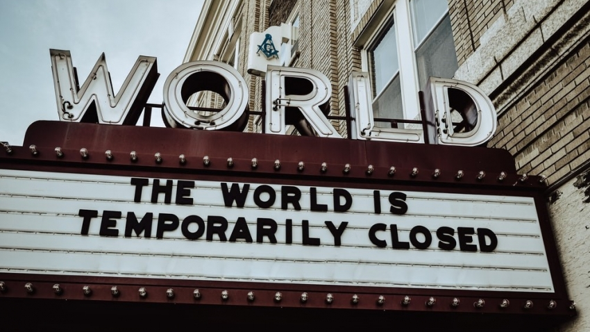 cinema marquee with sign displaying the words THE WORLD IS TEMPORARILY CLOSED
