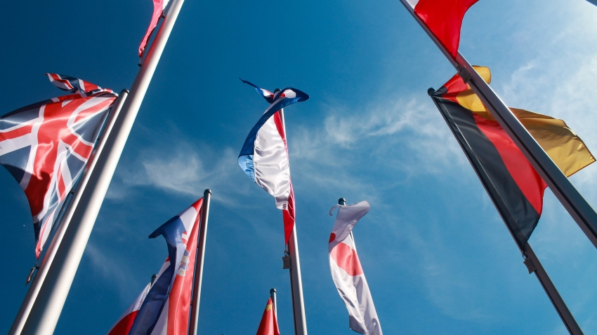 colourful flags silhouetted against a blue sky