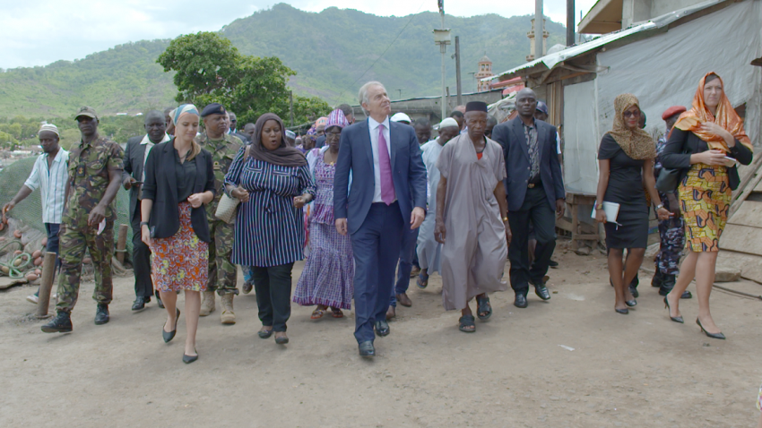 Group of people shown walking through a village