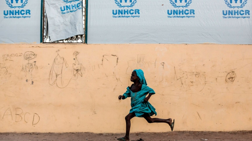 A young girl runs in front of a UNHCR banner
